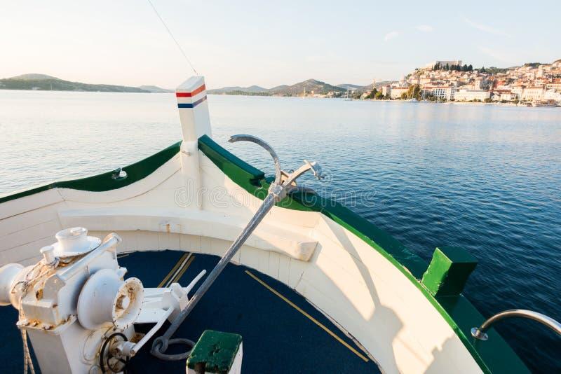 Vista della barca, prua della nave con l'ancora tradizionale, vecchia città storica mediterranea nel fondo fotografia stock