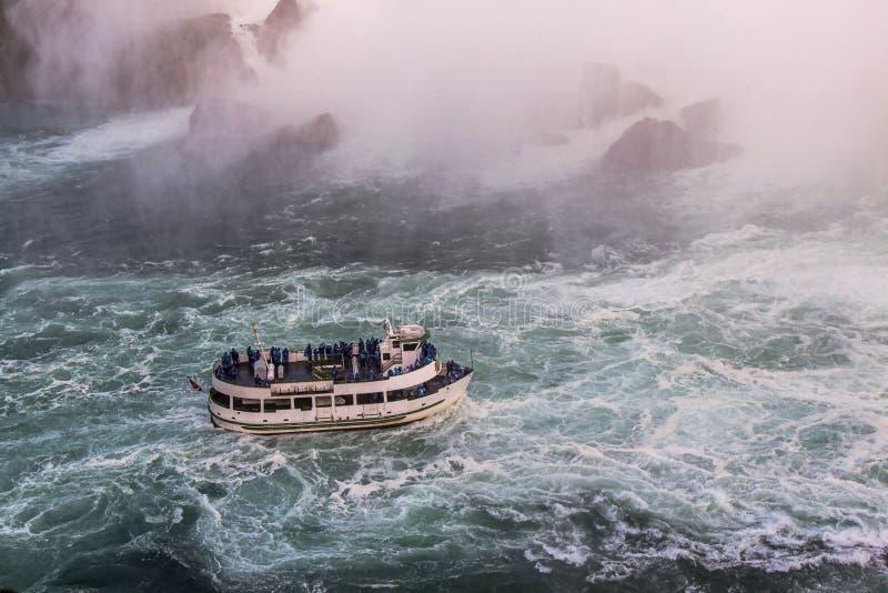 Vista della barca turistica sulle onde di brontolio del cascate del Niagara Concetto di turismo fotografia stock libera da diritti