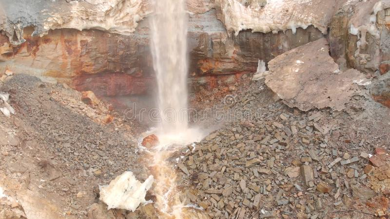 Vista della cascata su fondo di roccia minerale sporca azione La cascata sporca gocciola giù la parete marrone mineralogica della immagine stock libera da diritti