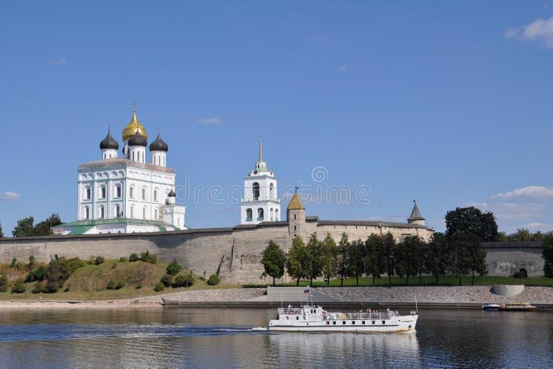 Vista della cattedrale della trinità nel Cremlino di Pskov dal grande fiume, su cui la nave naviga un giorno di estate, la Russia immagine stock libera da diritti