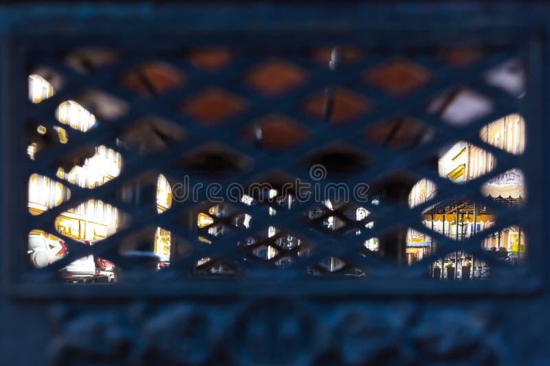 Vista della città attraverso la grata in ferro battuto fotografia stock libera da diritti