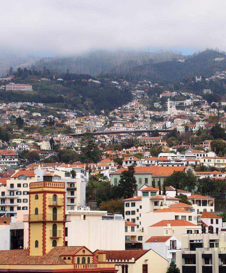 Vista della città di Funchal in Madera con la vecchie chiesa e case con il ponte e le montagne della strada nella distanza immagine stock libera da diritti