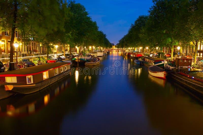 Vista della città di notte del canale di Amsterdam con la casa galleggiante fotografia stock