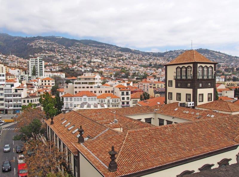Vista della citt? di Funchal in Madera con le costruzioni e gli alberi della molla contro un fondo delle montagne e del cielo nuv immagine stock