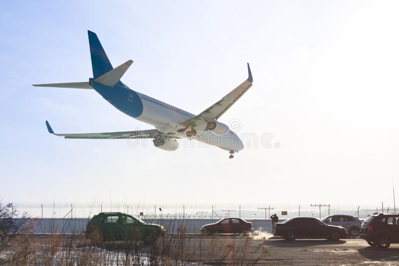 Vista della coda dell'aeroplano di atterraggio Aerei che sorvolano strada principale Strada con alto traffico vicino alla pista d fotografia stock libera da diritti