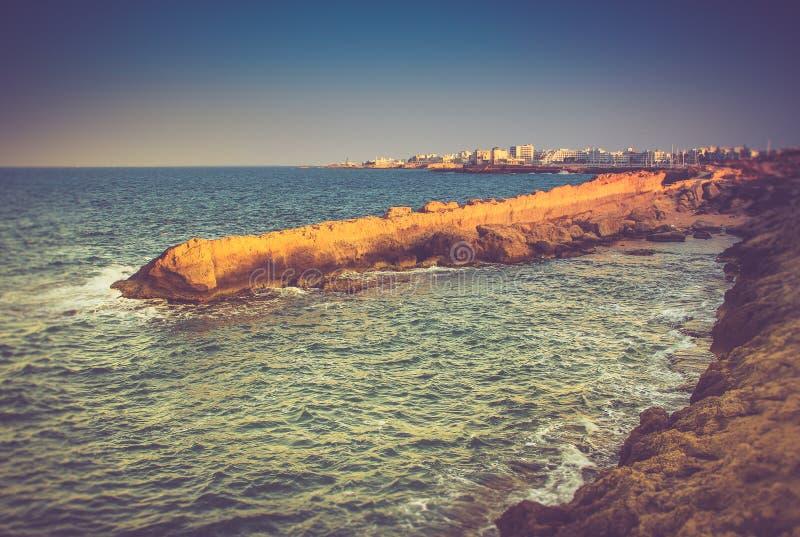 Vista della costa rocciosa, delle onde di schiumatura del mare e della città nella distanza al tramonto immagini stock