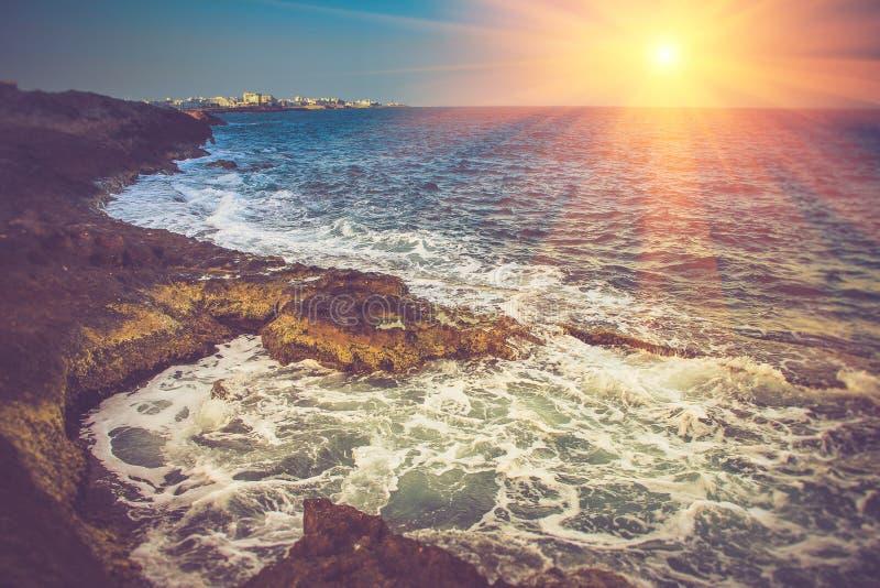 Vista della costa rocciosa, delle onde di schiumatura del mare e della città nella distanza al tramonto fotografia stock