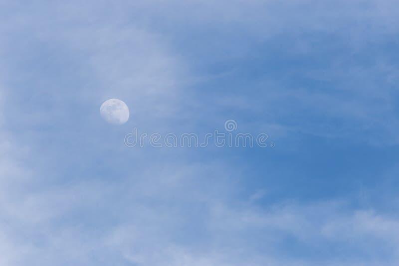Vista della luna attraverso alcune nuvole nel cielo blu immagine stock