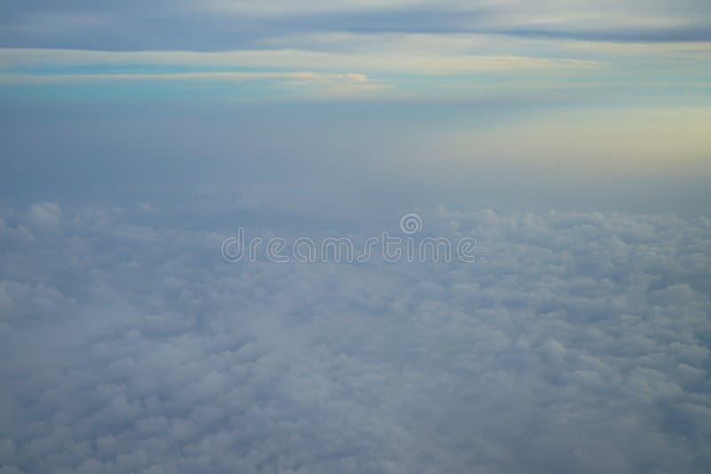 Vista della nuvola bianca astratta vaga con cielo blu e del fondo leggero di alba dalla finestra dell'aeroplano immagine stock