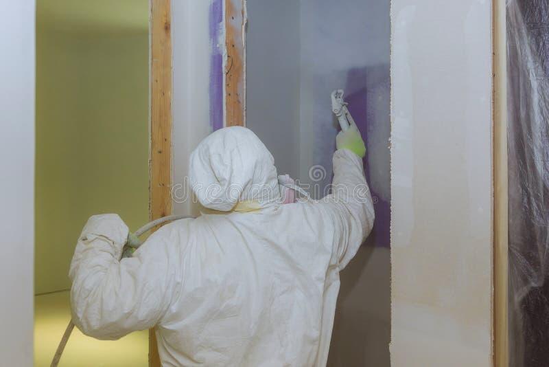 Vista della parete della pittura dell'uomo della pittura Facendo uso della pistola a spruzzo dalla fine laterale sulla vista immagini stock