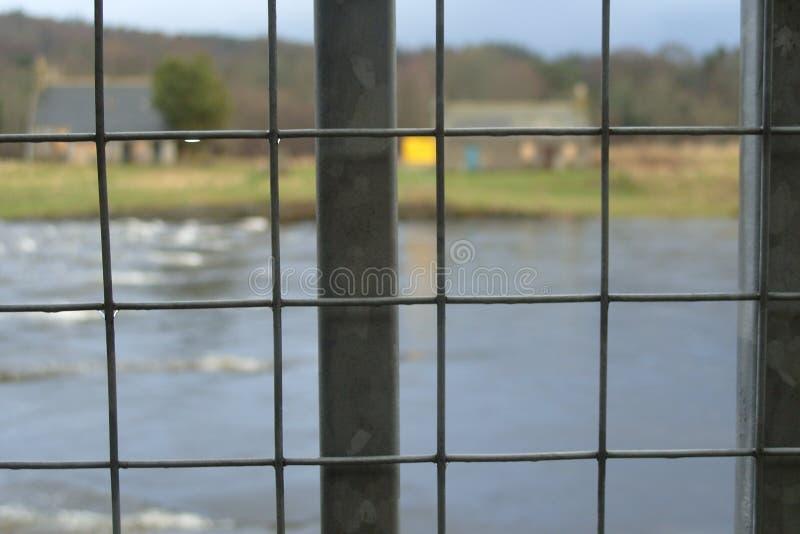 Vista della recinzione di acciaio in primo piano con fondo del fiume fotografia stock