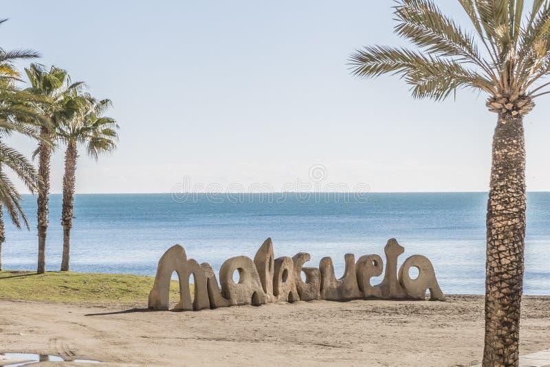 Vista della spiaggia con le palme ed in pietra il nome di Malaga fotografia stock libera da diritti