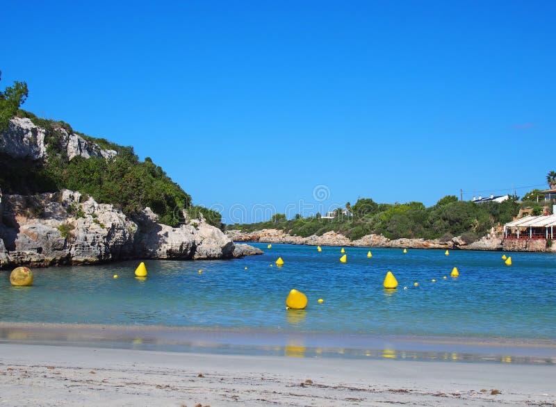 Vista della spiaggia e della baia a Cala Santandria in Menorca con gli indicatori gialli della barca in un mare e in un surroundi fotografie stock libere da diritti