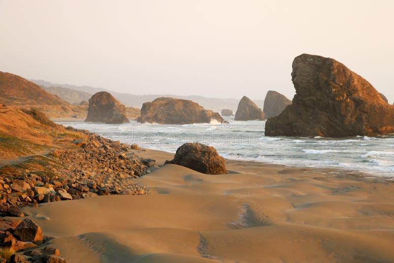 Vista della spiaggia sabbiosa e delle rocce durante il tramonto nell'oceano Pacifico fotografie stock