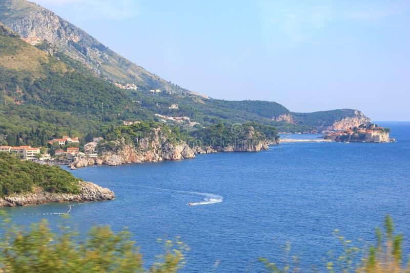 Vista delle baie del mare, della città di Przno e dell'isola di Sveti Stefan nel Montenegro dal bus che si passa il litorale immagini stock libere da diritti
