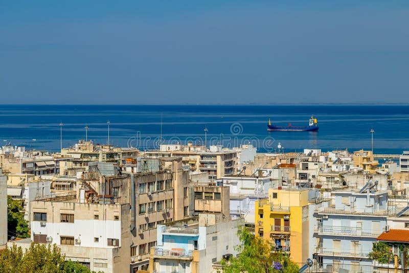 Vista delle Camere nella città greca di Patrasso e del mare con la nave da carico immagine stock libera da diritti