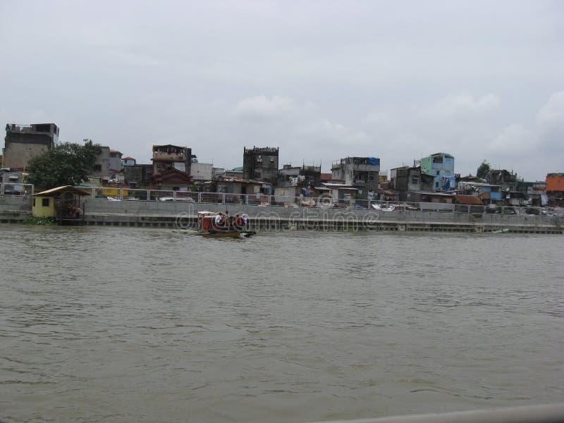 Vista delle case e del traghetto lungo il fiume di Pasig, Manila, Filippine fotografia stock libera da diritti
