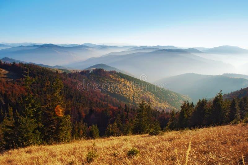 Vista delle colline di una catena montuosa fumosa coperta nel rosso, arancia a fotografia stock