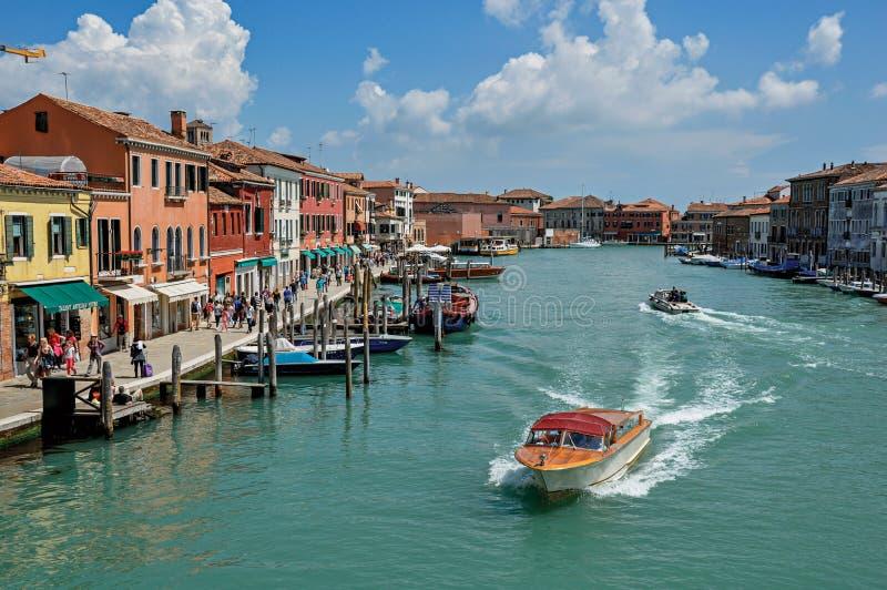 Vista delle costruzioni, davanti al canale, con la gente e le barche in Murano fotografia stock libera da diritti