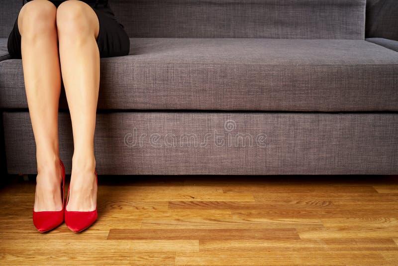 Vista delle gambe esili perfette di una donna di affari in tacchi alti sexy rossi che si siedono sullo strato fotografie stock