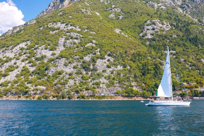 Vista delle montagne boscose verdi e mare blu, cielo blu e nuvole bianche e un yacht fotografie stock
