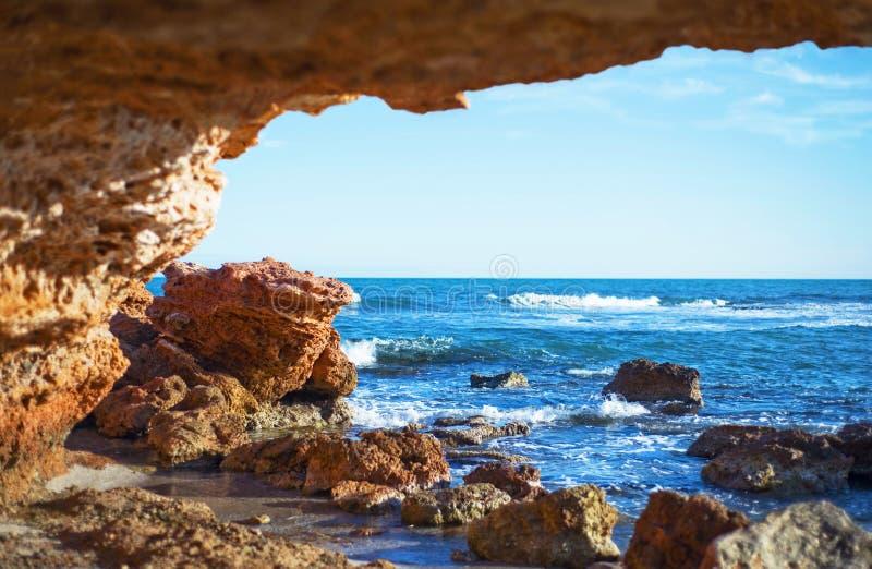 Vista delle onde del mare e del cielo da una caverna di pietra fotografia stock libera da diritti