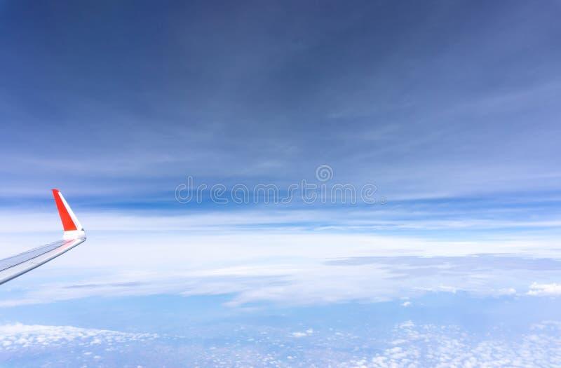 Vista dello scape del cielo dal sedile di finestra del vetro trasparente all'ala di aereo dell'aereo, viaggiando sulle nuvole e s immagini stock libere da diritti