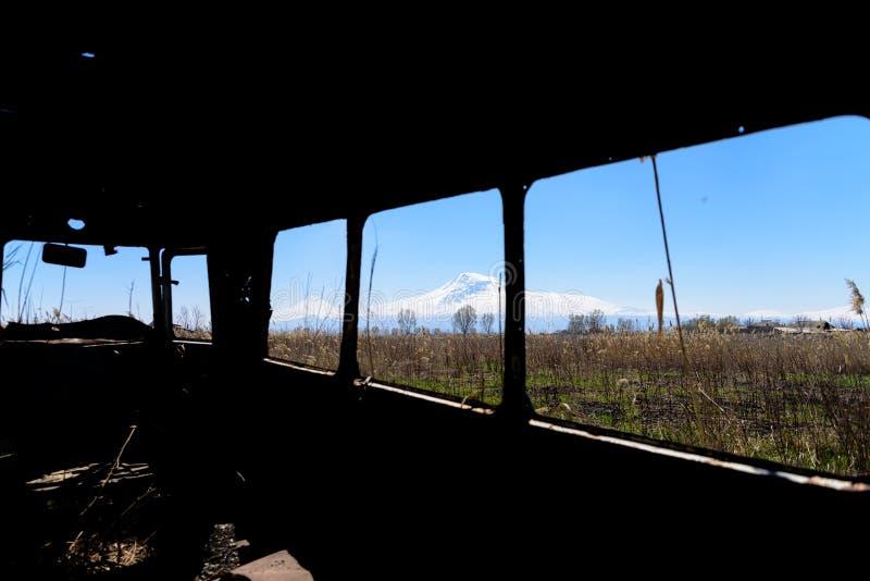 Vista desde adentro de un autobús ruso soviético viejo abandonado y oxidado en Armenia meridional imágenes de archivo libres de regalías