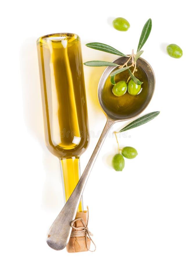 Vista desde arriba de un tarro con el aceite de oliva y algunas aceitunas verdes w fotos de archivo