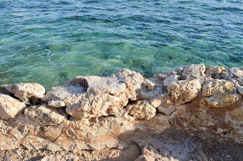 Vista desde arriba del mar azul, agua con una parte inferior coralina con una pared que desmenuza antigua vieja de piedra foto de archivo