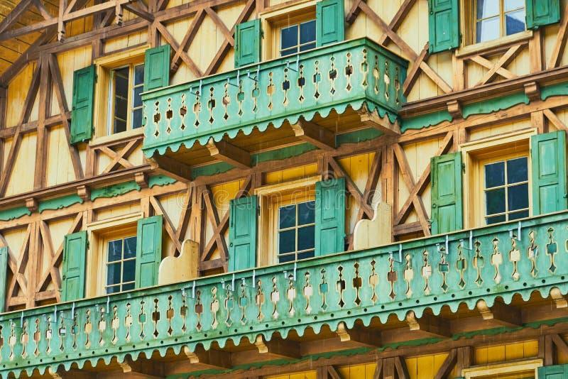 Vista detallada de una casa bávara tradicional con entramado de madera y balcones verdes de madera fotografía de archivo