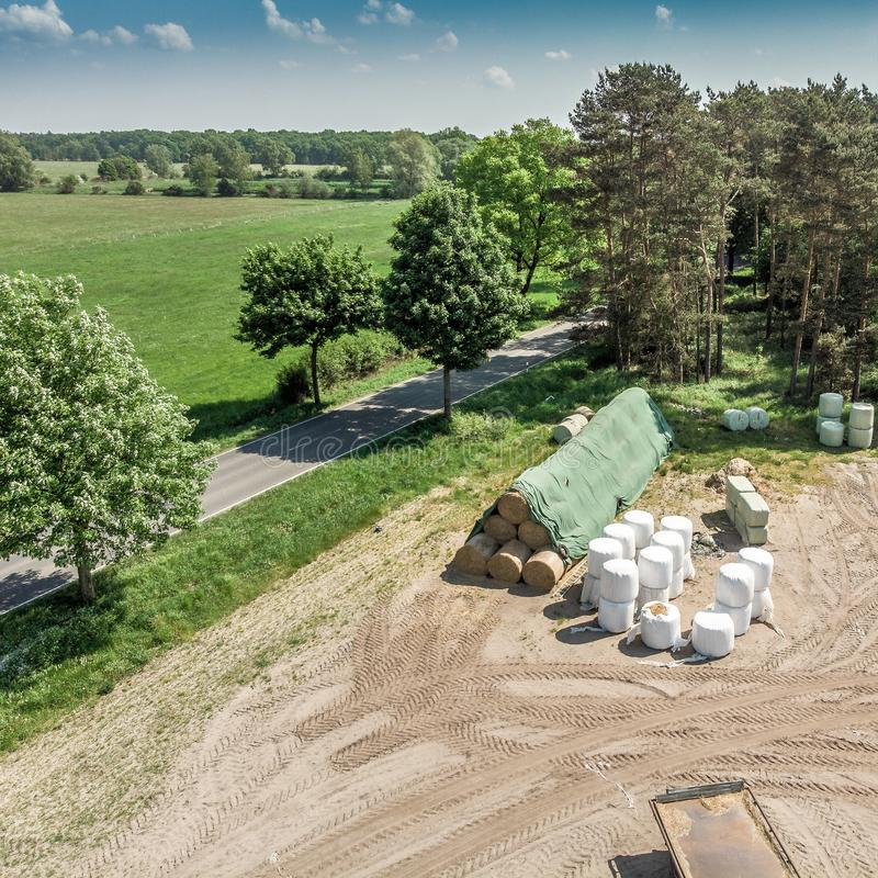 Vista dettagliata dall'aria di un posto di stoccaggio per un'azienda agricola, con silaggio, fieno e paglia, vista aerea fotografie stock