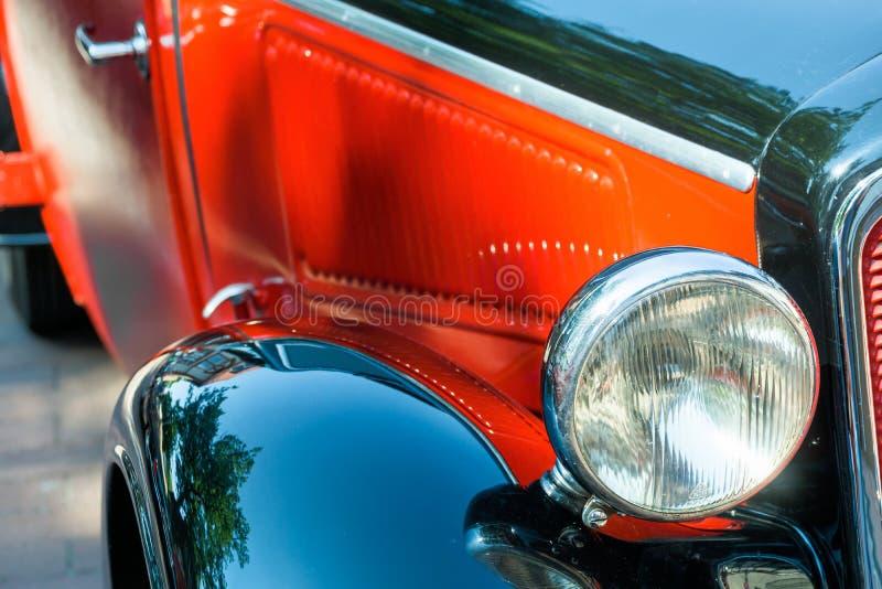Vista dettagliata di un veicolo storico con i fari liberi, il cofano rosso e le ali brillanti nere, Oldtimer-festival immagini stock