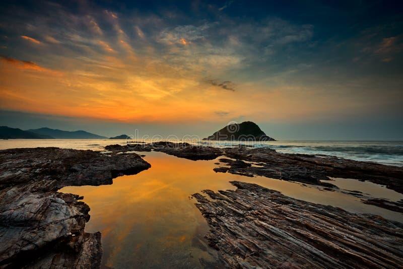 Vista di alba con vista sul mare e rocce immagini stock
