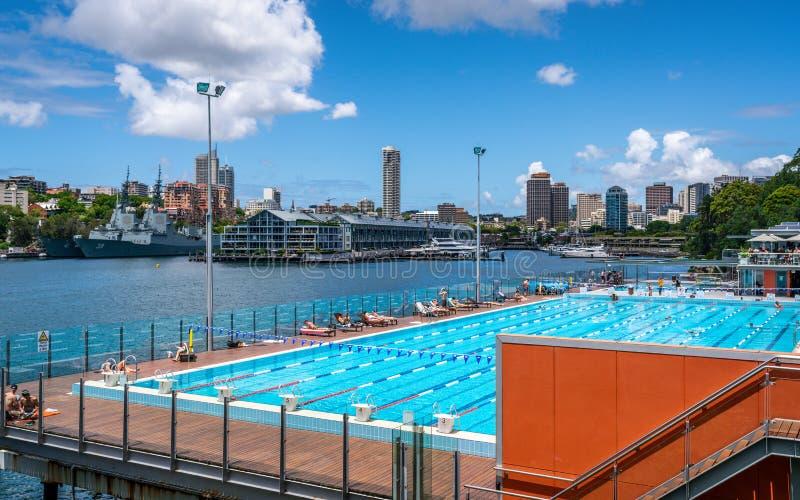 Vista di Andrew Boy Charlton Pool all'aperto con il molo del dito di Woolloomooloo e della gente e della baia nel fondo a Sydney  fotografia stock