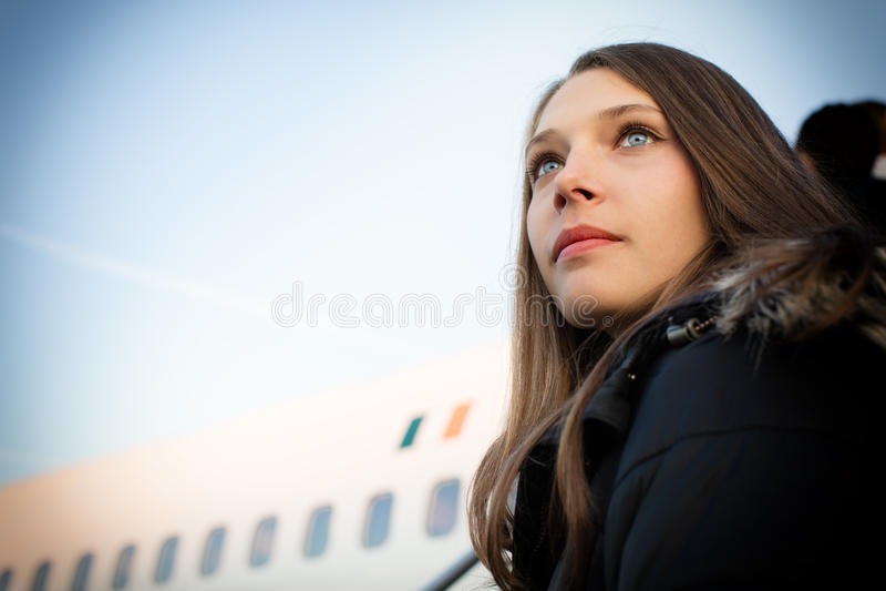 Vista di angolo basso del ritratto della donna davanti all'aeroplano contro il cielo immagini stock libere da diritti