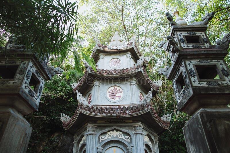 vista di angolo basso del tempio orientale tradizionale antico fra le piante verdi, Da fotografia stock libera da diritti