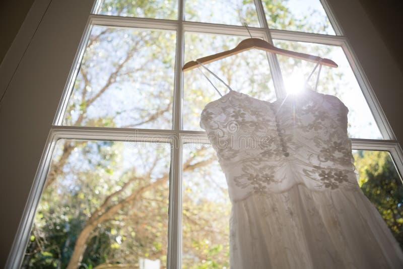 Vista di angolo basso del vestito da sposa che appende sulla finestra nella sala fotografia stock libera da diritti