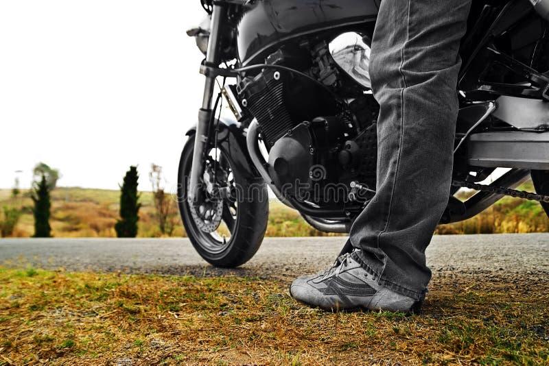 Vista di angolo basso della bici di guida dell'uomo contro il chiaro cielo fotografia stock