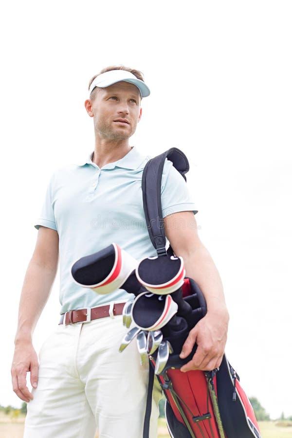 Vista di angolo basso della borsa di club di golf di trasporto dell'uomo premuroso dell'mezzo adulto contro il chiaro cielo immagini stock libere da diritti