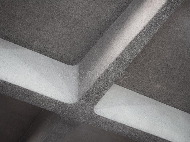 Vista di angolo basso della trave trasversale concreta massiccia nella forma di incrocio sul soffitto all'interno immagine stock