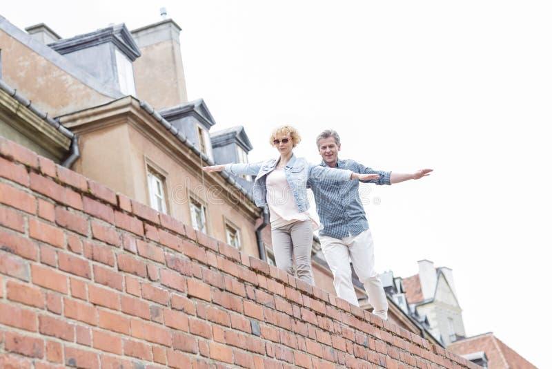 Vista di angolo basso delle coppie di mezza età con la camminata stesa di armi sul muro di mattoni contro il chiaro cielo fotografie stock libere da diritti