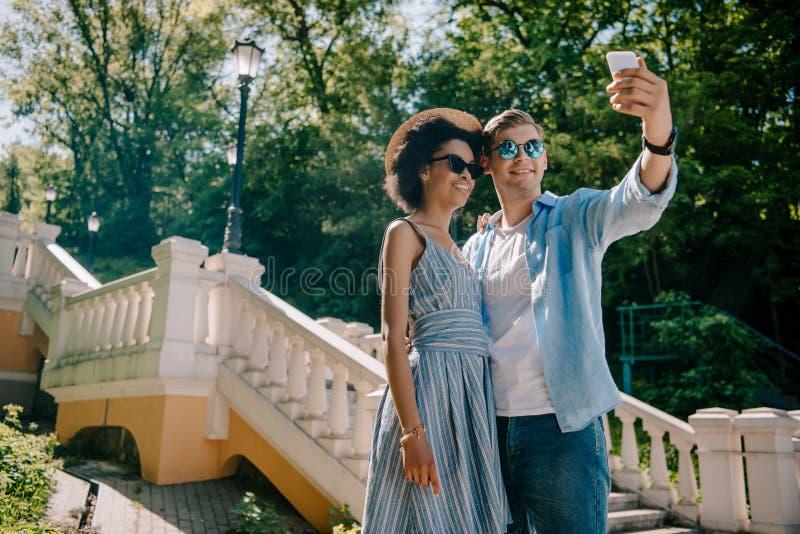 vista di angolo basso delle coppie multietniche sorridenti in occhiali da sole che prendono selfie sullo smartphone immagini stock