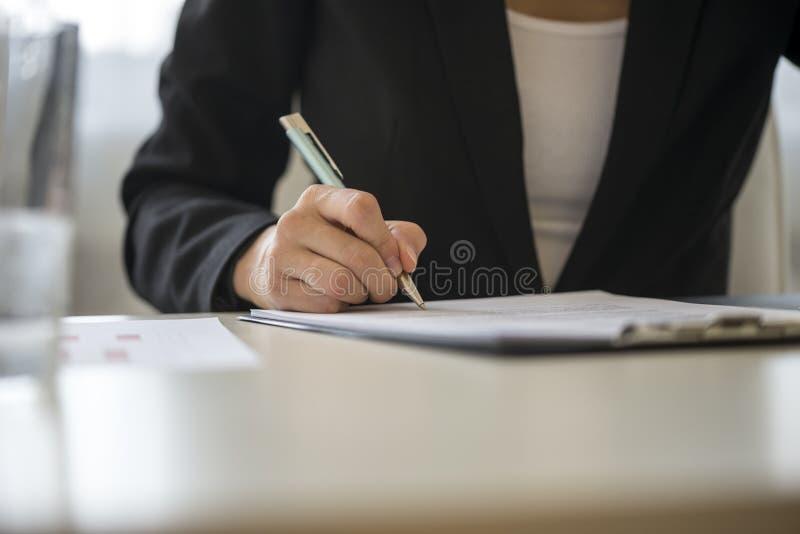 Vista di angolo basso di un contratto di firma della donna immagine stock