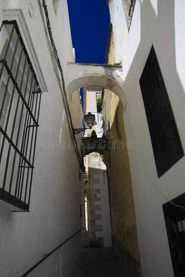 Vista di angolo basso sul vicolo vuoto stretto con le facciate delle case bianche e dei punti di sopra che contrappongono con il  fotografia stock libera da diritti