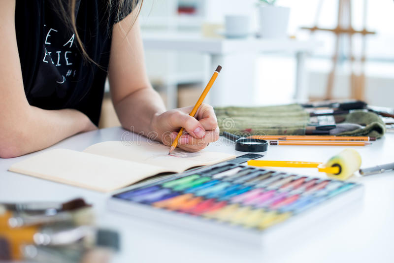 Vista di angolo del primo piano di un progetto femminile del disegno del pittore allo sketchbook facendo uso della matita Artista fotografia stock