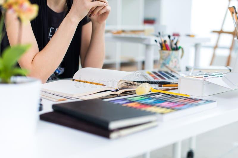 Vista di angolo del primo piano di un progetto femminile del disegno del pittore allo sketchbook facendo uso della matita Artista immagine stock libera da diritti