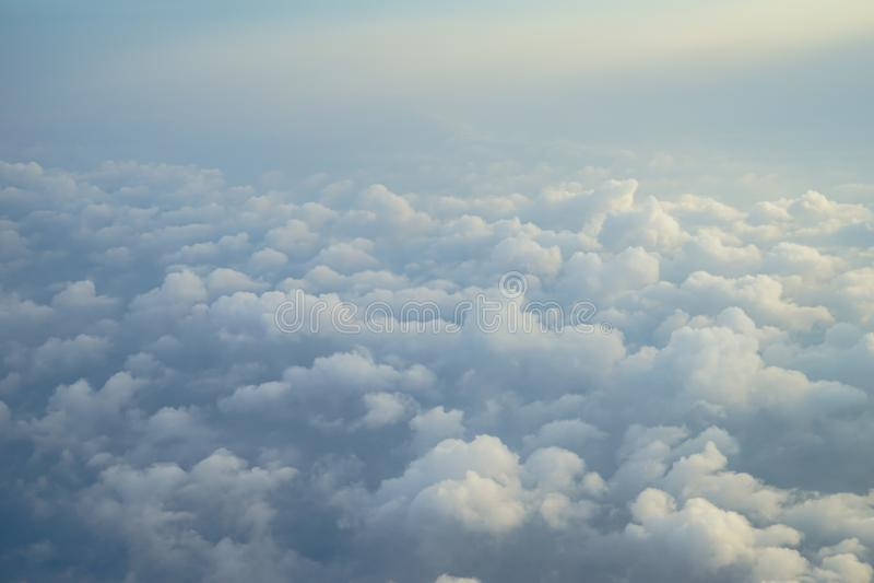 Vista di bella nuvola bianca astratta lanuginosa vaga con cielo blu e del fondo leggero di alba dalla finestra dell'aeroplano fotografia stock