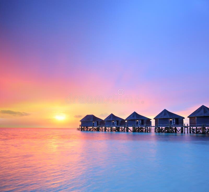 Vista di bello tramonto su un'isola delle Maldive e sulle ville dell'acqua fotografia stock