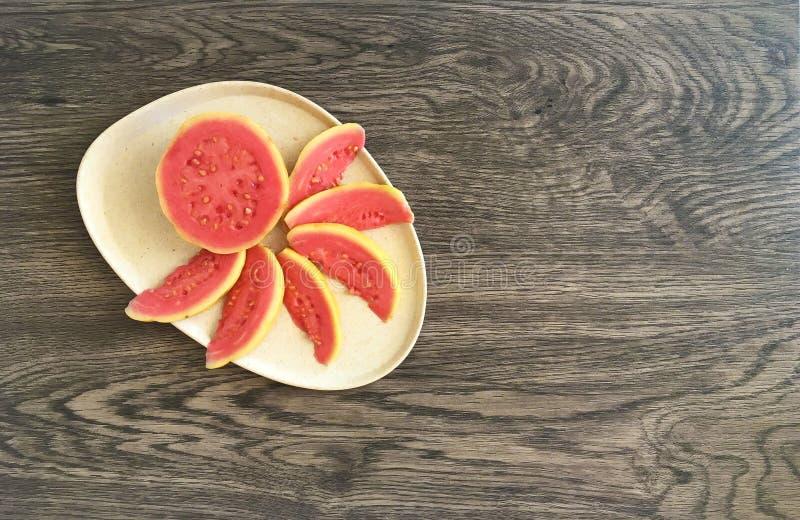 Vista di Birdseye di di guaiavo tropicale affettato su un piatto amichevole di Eco fotografie stock